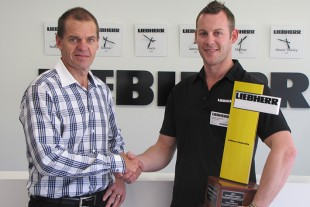 Trent Wehr (Director Mining, Liebherr-Australia) presents Michael Hodgson with his award.