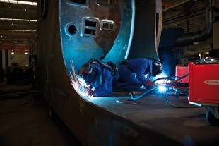 The apprentices weld a seam on a ship crane.