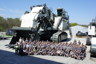 Employees of Liebherr-Mining Equipment Colmar SAS in front of the R 9800 crawler excavator