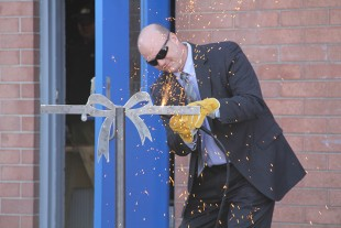 "Cort Reiser, Liebherr executive vice president of manufacturing and warehouse logistics, commemorated the opening of the welding lab by ""cutting"" a steel ribbon made by Liebherr employees."