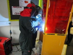 Apprentice Welder, Kristian Small showing a student how to weld on the portable welding booth