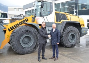 Mr Martin Gschwend (left), Sales Director, Liebherr-Werk Bischofshofen, hands over eight new wheel loaders to Dr. Matthias Jacob (right), Managing Director of construction company WOLFF & MÜLLER. In the background, the new L 566 wheel loader can be seen.