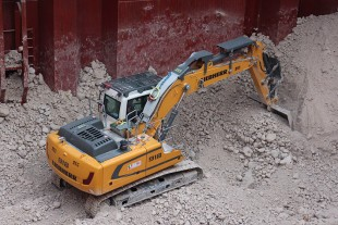 The Liebherr R 918 crawler excavators work inside the cargo holds of freight ships in order to restack various cargo so that they can be unloaded.