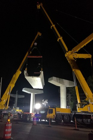 Hoisting a U-shaped beam onto the supports.