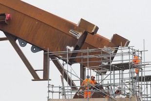 Massive – The structural steel workers in the picture demonstrate the dimensions of the bridge arch which measures 90 metres in length and weighs in at 560 tonnes and is almost in position in this photograph.