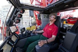 Keeping an overview: Crane operator Peter Stricker watching numerous monitors in the spacious cab of the LR 11000.