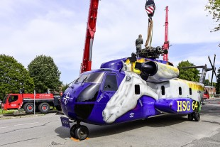 Attaching the lifting equipment to the lifting beam on the transport helicopter's main rotor.