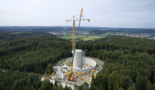 An LTM 11200-9.1 operated by the Max Bögl Group assembles a Liebherr top-slewing crane on the energy storage project site at Gaildorf.