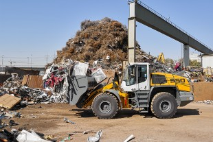A Liebherr L 550 Xpower wheel loader moving materials in a scrap yard