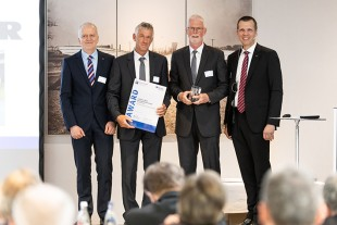 Dr-Ing Herbert Pfab (2nd from left), Head of Development, and Johann Stickler (2nd from right), Managing Director and Technical Director, of Liebherr-Werk Bischofshofen GmbH, proudly accept the EuroTest Prize 2019 for the active personnel detection.