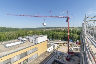 MK 140 Liebherr mobile construction crane exchanging air conditioners at a hospital in Heidenheim.