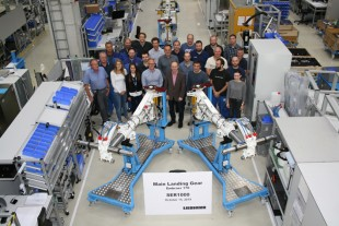 Members of the Liebherr-Aerospace team proudly present the Embraer 170 main landing gear shipset.