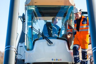 (l-r) His Royal Highness, The Duke of Kent, test drives a Liebherr Reachstacker (LRS 545) crane during his visit to the company's Sunderland plant.