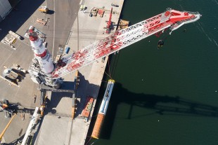 "Liebherr TCC 78000 heavy-duty crane loads 72 monopiles for the largest Danish offshore wind farm ""Kriegers Flak""."