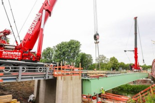 The steel girders weighing 168 tonnes are carefully placed on the abutments.