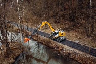 The Liebherr LH 22 M Industry Litronic material handler equipped with Liebherr stick extension and Westtech Woodcracker® C250 is available for reaching trees and bushes that are far away.