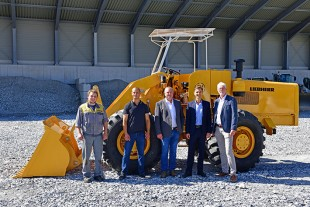 Current and retired employees of the Liebherr Bischofshofen facility (Austria) in front of the restored wheel loader LSL 1500 .