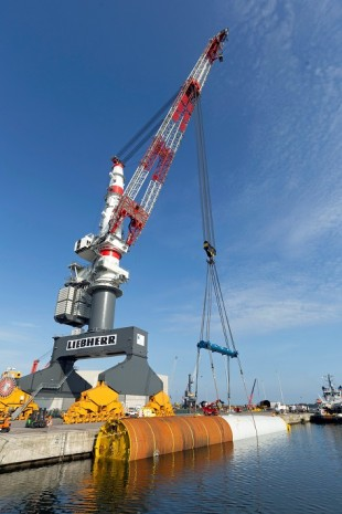 Almost cautiously, the TCC 78000 lays one of 72 monopiles, each weighing about 800 tons, into the Rostock harbour basin.