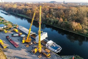 The crane operators unload the turbine from the barge in Oberhausen and slew the heavy load between the two cranes.