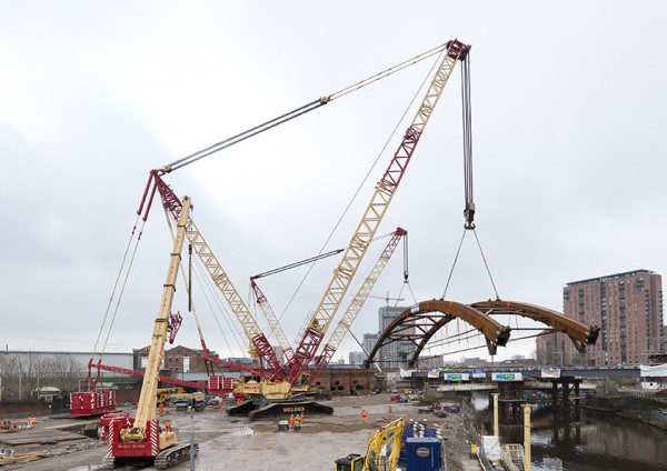 Off they go – after picking up the load, both cranes initially move a step closer to the bank of the River Irwell.